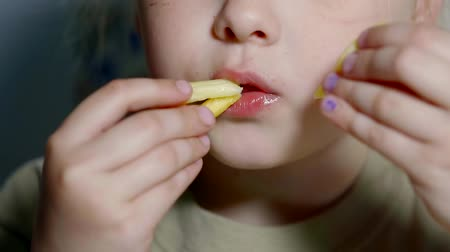 fries : Close up shot of a young little girl eating french fries.