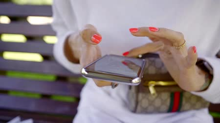 sending : close up. well-groomed womens hands with high-quality manicure uses a cell phone with a touch screen for access to the social network