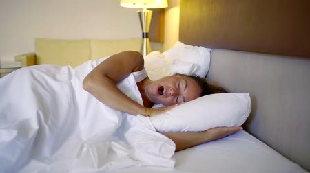adormecido : middle-aged woman wakes up in the morning in a comfortable bed in the hotel Vídeos