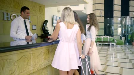 cortes : At the reception, a group of women with a suitcase happily meets the hotel staff. Business, travel and people concept