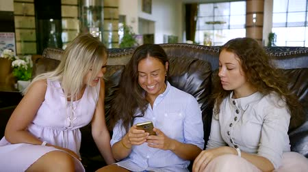 lobi : Three beautiful smiling friends relax in the hotel lobby with a phone