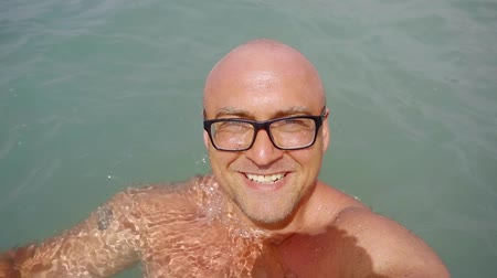 calções de banho : 500 frames a second. Portrait of a bald happy man in the sea. Enjoy the long-awaited vacation at the resort. wear a wet hat on your head.