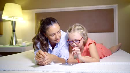 головоломки : mom and daughter in glasses playing lying on their stomachs on the bed in the tablet computer