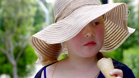 окропляет : girl in straw hat eat one flavour of ice cream in the hot summer day Стоковые видеозаписи
