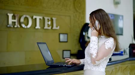 vendégszeretet : Executive officer of the hotel business woman standing at the reception Desk and working on a laptop talking on the phone.