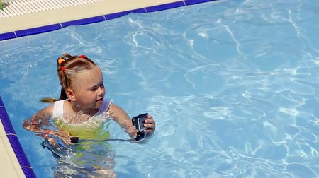 impermeabile : bambina in piedi in piscina in acqua e imposta una action camera su un bastone selfie per registrare il suo blog video personale