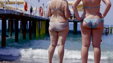 bulimia : two women with obesity and cellulite are on the beach overlooking the sea. diet and weight loss concepts Stock Footage