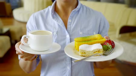 kandovaný : Close - up view of a beautiful cupcake on a saucer and a Cup of invigorating cappuccino. Woman holding a plate of cake and coffee