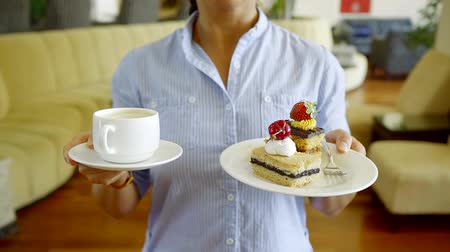 kandovaný : Close - up view of a beautiful cake with strawberries on a saucer and a Cup of invigorating cappuccino. Woman holding a plate of cake and coffee Dostupné videozáznamy