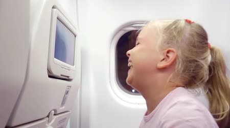 nézett : A little girl traveling in an airplane, sitting in her seat, playing with a built-in video player and choosing a cartoon watched by a parent