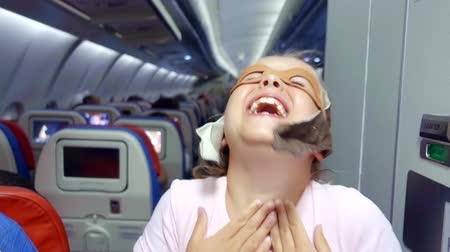 nézett : cheerful happy child girl playing in the plane in the pilot wearing a classic helmet and imitation glasses