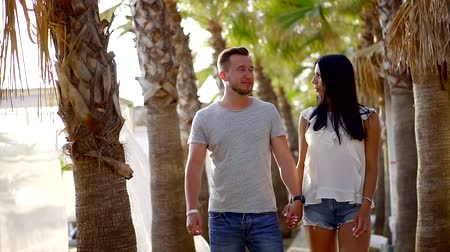 darling : cute young couple strolling along the palm trees in the tropical garden