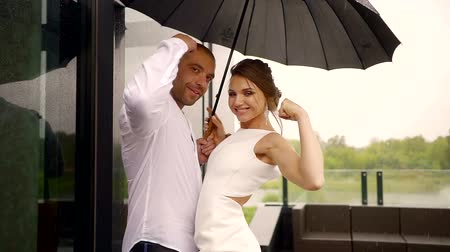 comes : cheerful sports couple of newlyweds posing in the rain standing under an umbrella demonstration of a bicep in a pose in front