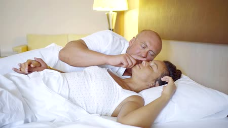 tartózkodás : middle-aged couple sleeping in bed, loving husband hugs wife lying on white lingerie with eyes closed, enjoying smile in light sleep in the morning before waking up