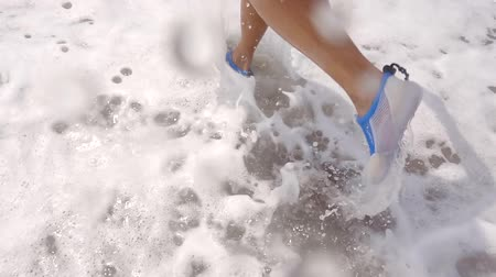 façanha : close up shot of the womans feet, the lady is doing sports in seawater during the summer vacations