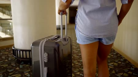 lobby : close up shot of the womans body, who walks around the hotel with a suitcase, the lady is populated