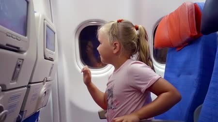 мультфильмы : funny girl watching cartoons on TV in the chair in the plane