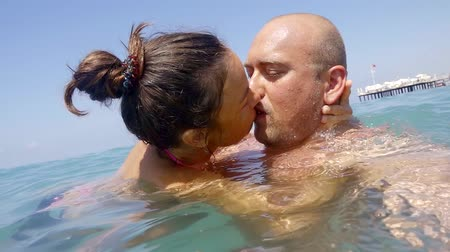 intim : a young woman gently and passionately kisses her husband, the couple is in the sea