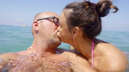 intim : spouses kiss each other gently during a voyage in the blue ocean Stock Footage