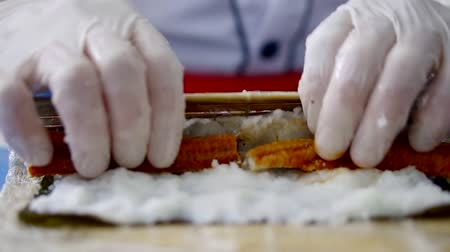 professionally : Preparation of a sushi roll in restaurant, close up on chef hands