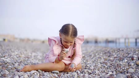 заботливый : a cute and funny girl sits on a stony beach and fingings the pebbles in her hands, she wants to get up