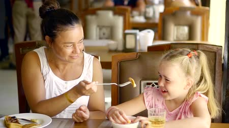 основное блюдо : A young woman and her daughter eat at the table during dinner, they are at the hotel
