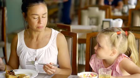 villa : A young woman and her cute and pretty daughter are at the dinner table and talking, they are in a restaurant