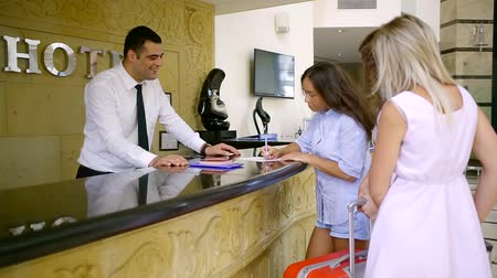 cortes : three tourists women are check-in in hotel, brunette girl is filling papers, hotel manager is smiling