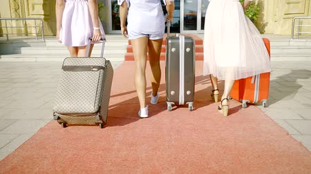 в середине : back view of three slim women with suitcases are approaching to stairs of hotel entrance in sunny day