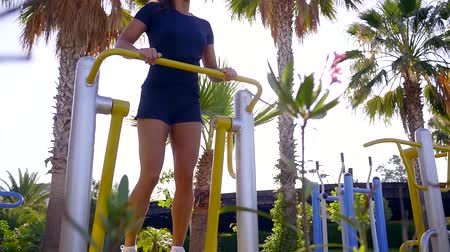 move well : adult athletic woman is working out on elliptical trainer outdoors in a tropical garden, moving her legs Stock Footage