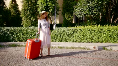 voyager : alone woman with luggage is waiting her two friends women in sunny street, meeting and hugging each other