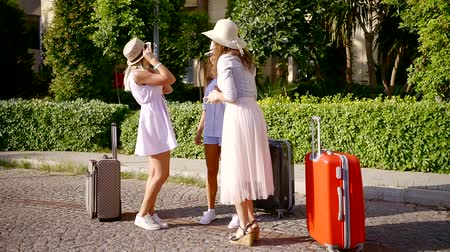 voyager : three cheerful adult woman are standing in a yard of hotel in sunny day and laughing, their luggage is standing near