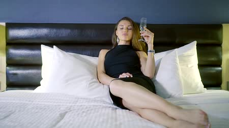 сверкающий : beautiful young woman is lying on a white bed in a bedroom, wearing in black evening dress, drinking wine from glass