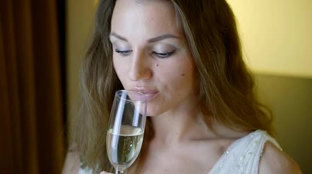 tasting : pretty brown-haired woman is drinking sparkling wine from crystal glass alone in room, focus is moving Stock Footage