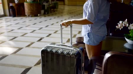 проведение : brunette girl is wearing straw hat, shorts and shirt is rising from a couch in a vestibule, taking her suitcase and going out Стоковые видеозаписи