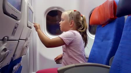 aircraft cabin : little child girl is passenger of airplane, is sitting on a seat in cabin, looking on a display in chair