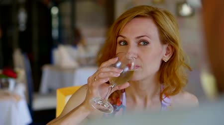 jubileu : pretty ginger woman is tasting white wine from goblet in restaurant, enjoying and refreshing