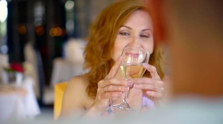 jubileu : pretty joyful woman is looking through a glass with white wine in her friends in a restaurant during lunch