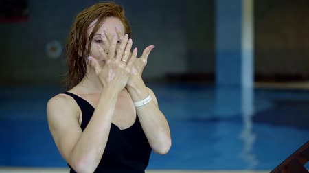 melanin : adult redhead woman with vitiligo on skin is demonstrating her arms and palms, posing in background of swimming pool Stock Footage