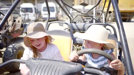 quadbike : two children girls are wearing big summer hats are sitting inside a quad bike in sunny summer day in parking Stock Footage