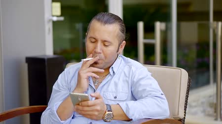 fotel : man is resting on terrace, sitting in armchair and smoking cigarette, looking on a screen of mobile phone