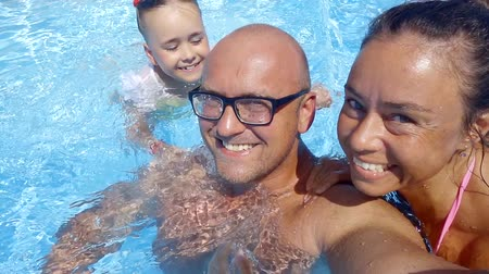 him : happy parents with little daughter are bathing in swimming pool in summer, man is filming himself