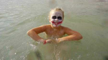 žolík : little girl with face art joker style is bathing in sea water and splashing in camera, shouting and grimacing