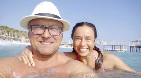 easily : happy adult husband and wife are floating in water near tropical ocean beach in summer holidays Stock Footage