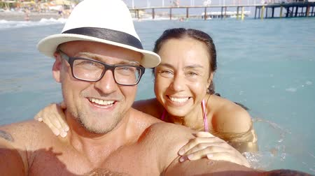 tuzlu : happy married couple are standing in sea water in summer day, filming themselves on camera and smiling Stok Video