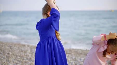 each other : little sisters are playing together in seacoast with pebbles, standing against each other, holding stones Stock Footage