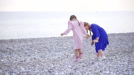 waterline : two little sisters are walking over pebble beach of sea, taking stones and running to waterline Stock Footage