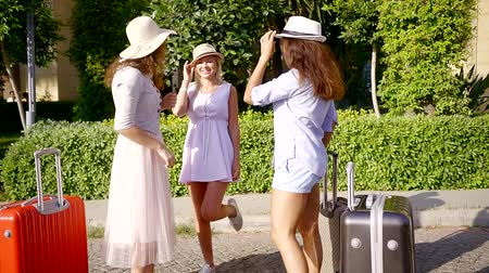 voyager : three joyful women friends are standing in courtyard of hotel in sunny summer day with baggage and gossiping