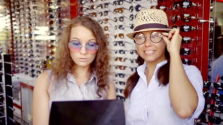 aro : young woman dressed funny, but stylish glasses and fooling around in the optics store