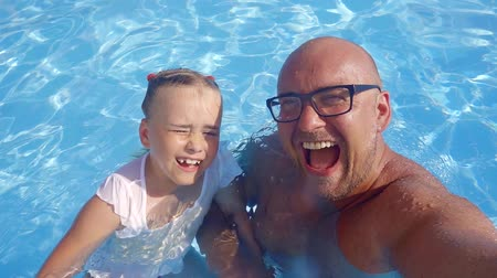 apaság : young and happy father is in the pool with his daughter, the girl is smiling